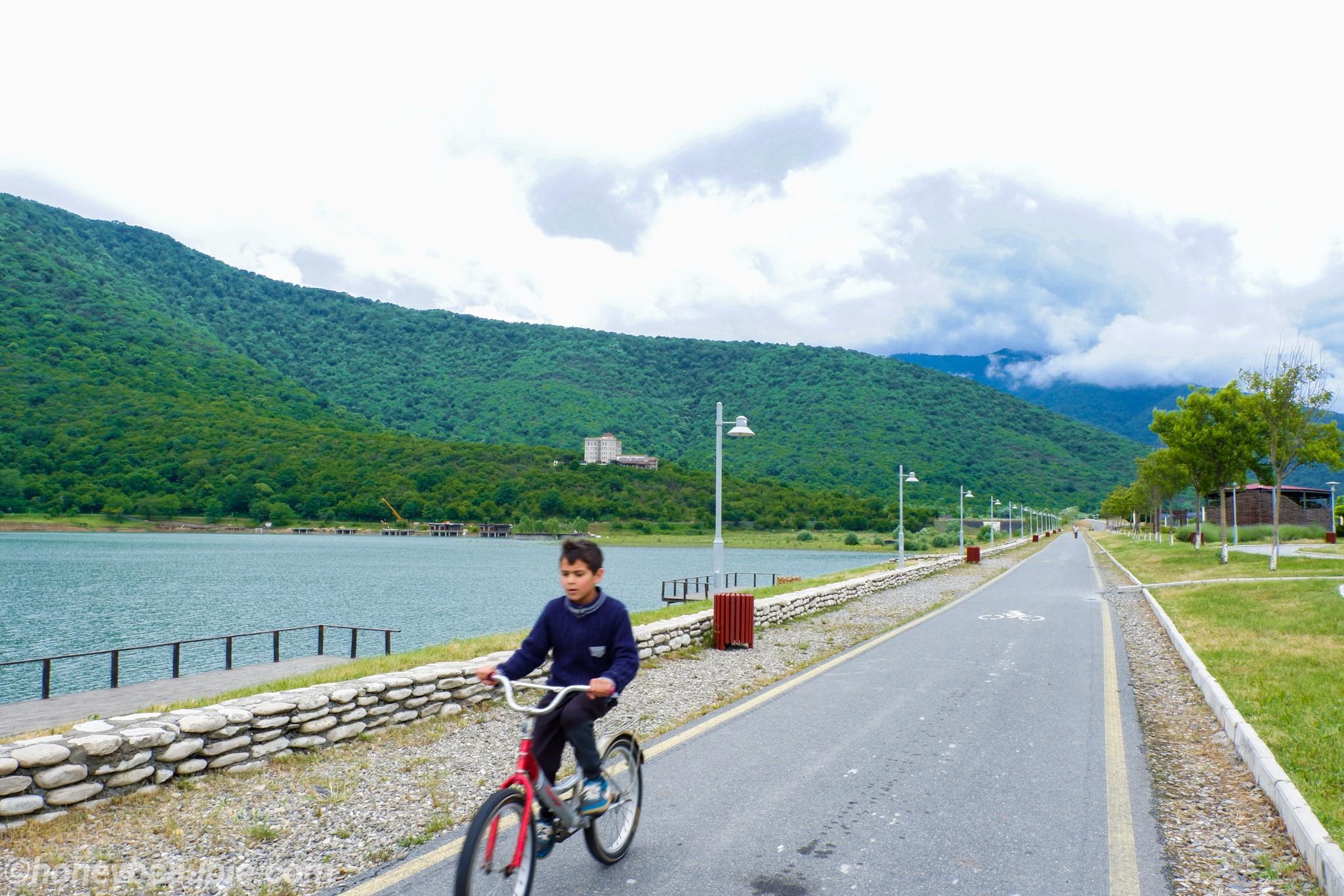 local-georgia-boy-riding-bicycle-ilia-lake-resort-georgia